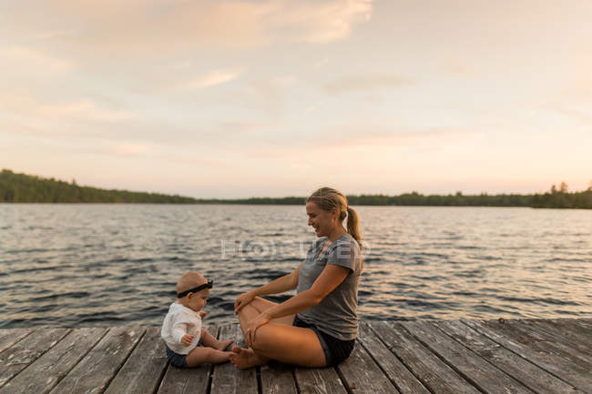 Mother sitting cross legged on lake pier with baby daughter — Stock Photo