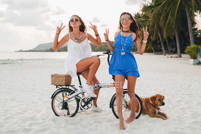 Retrato de duas jovens mulheres com bicicleta fazendo sinal de paz na praia de areia, Krabi, Tailândia — Fotografia de Stock