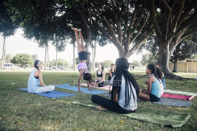 Школьницы практикуют йогу стоя на руках на школьной спортивной площадке — стоковое фото