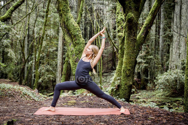 Young woman practicing yoga in forest — Stock Photo