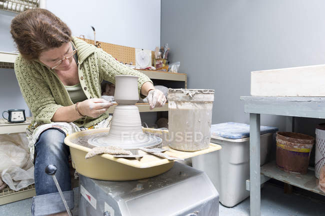 Woman working on potter wheel in studio — Stock Photo