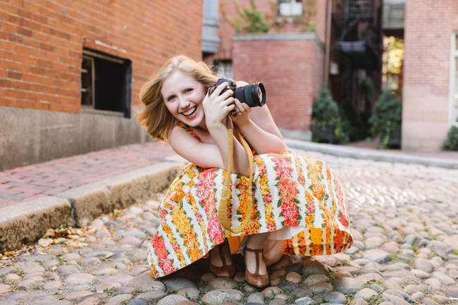 Young female photographer crouching with camera on cobbled street — Stock Photo
