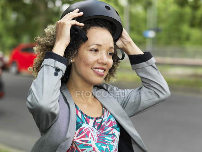Середині дорослу жінку надягаючи велосипедний шолом безпеки — стокове фото