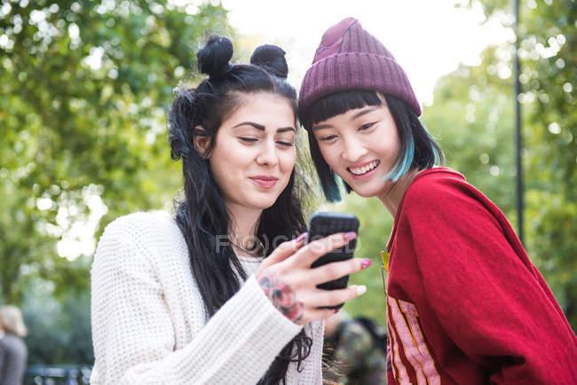Dos mujeres jóvenes y elegantes mirando el teléfono inteligente en el parque de la ciudad - foto de stock
