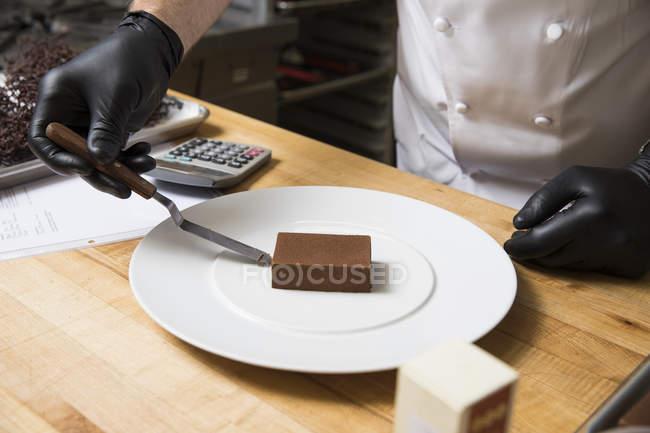 Recadrée vue du chef plaçant gâteau sur plaque — Photo de stock