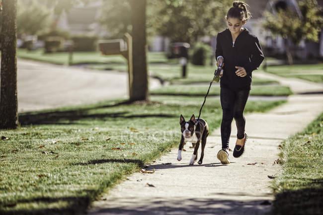 Jeune fille à marcher avec le chien le long de la voie — Photo de stock