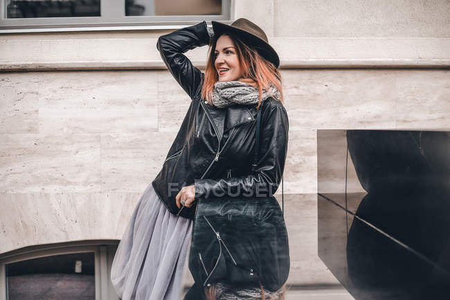 Woman in hat and leather jacket looking away — Stock Photo
