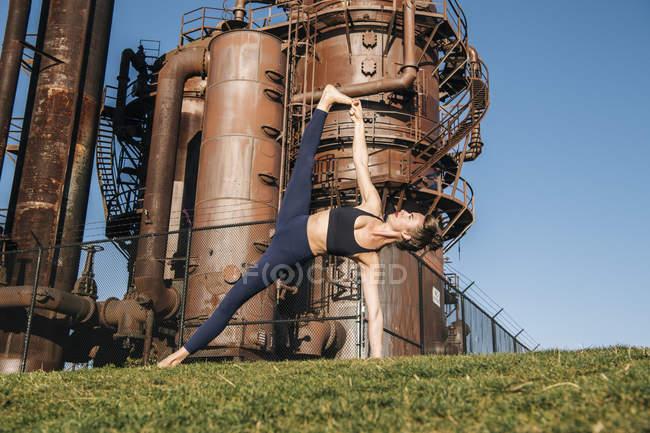 Молода жінка поблизу промислових робіт у позиції йоги — стокове фото