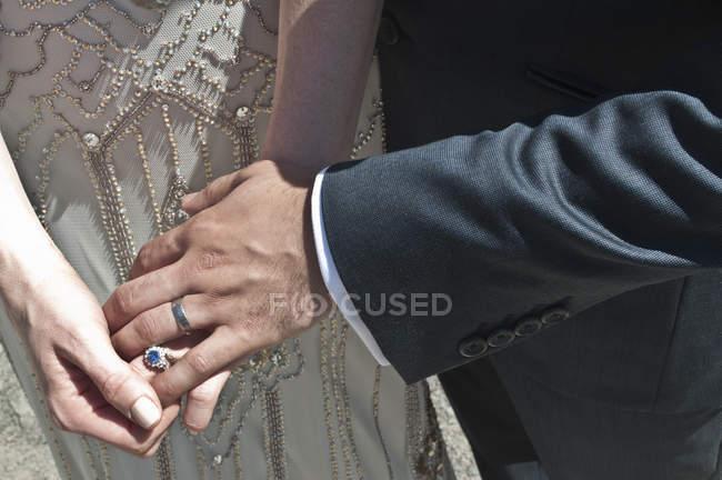 Mariée et le marié, main dans la main, gros plan, mi section — Photo de stock