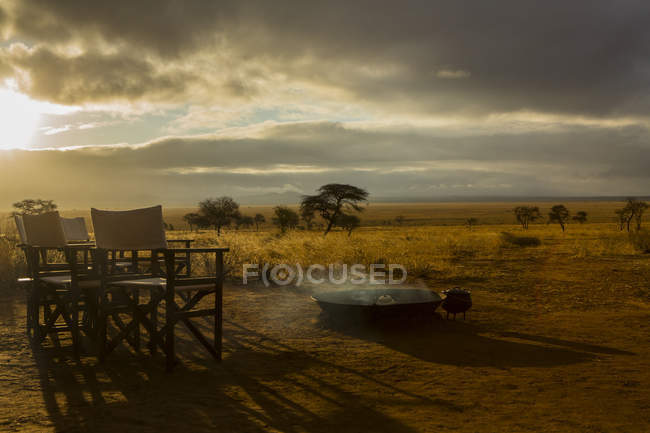 Camp fire and chairs in morning, Tarangire National Park, Tanzania, Africa — Stock Photo