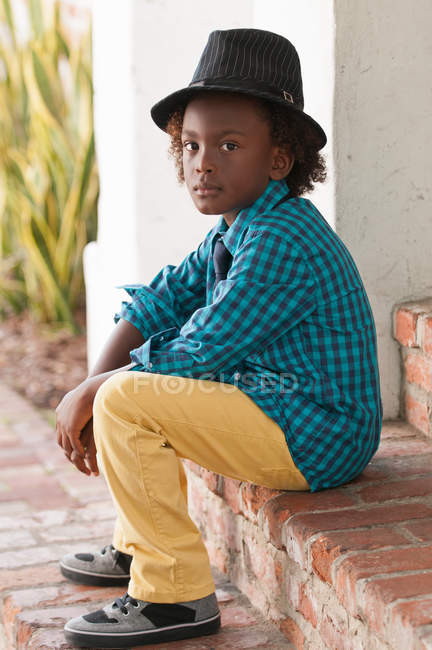 Portrait of young boy in fedora sitting outdoors — Stock Photo