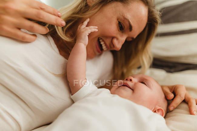 Donna sul letto a giocare con la figlia del bambino — Foto stock