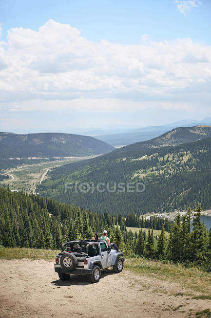 Road trip couple looking out at mountains from off road vehicle hood, Breckenridge, Colorado, USA — Stock Photo
