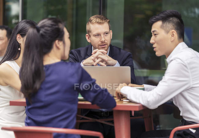 Four colleagues talking in outdoor cafe — Stock Photo