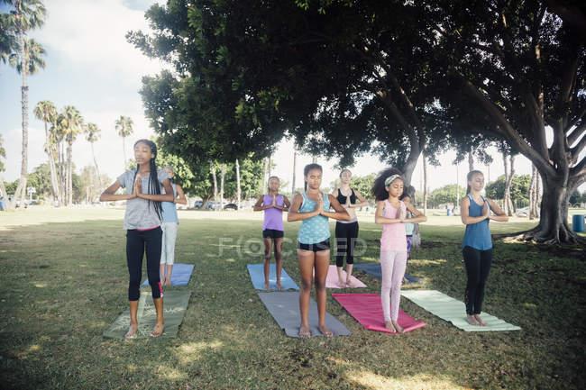 Школьницы практикующие йогу горная поза на школьной спортивной площадке — стоковое фото