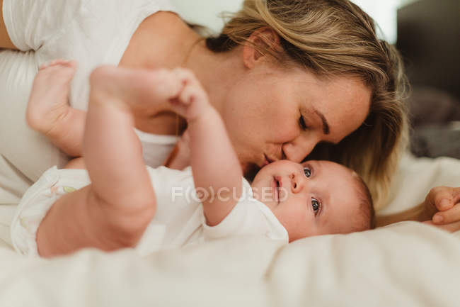 Woman kissing baby daughter on bed — Stock Photo