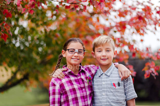 Siblings with arms around each other dressed up as nerd — Stock Photo