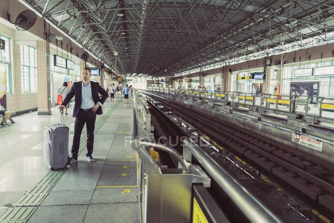 Далеких з видом на бізнесмена колісні валізи, стоять біля залізничного вокзалу — стокове фото
