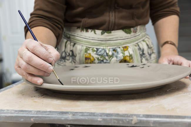 Mains de femmes peinture sur plateau d'argile — Photo de stock