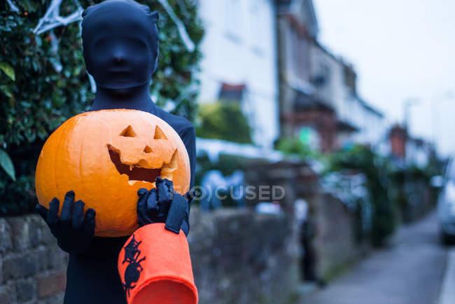 Portrait d'un garçon vêtu d'un costume d'Halloween, tenant une citrouille et jouant ou gâtant le seau — Photo de stock