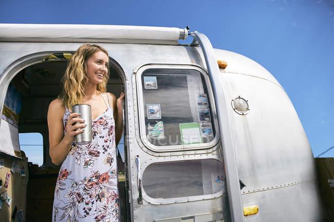 Junge Frau mit Kaffee mit Blick vom Airstream Tür — Stockfoto