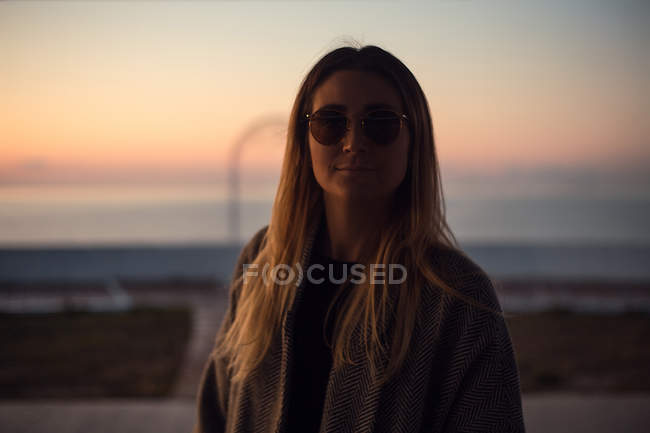 Portrait of woman in shade wearing sunglasses — Stock Photo