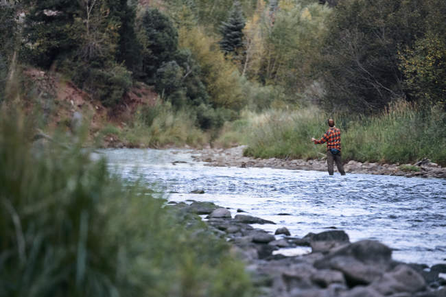 Homem de pé no rio e pesca — Fotografia de Stock