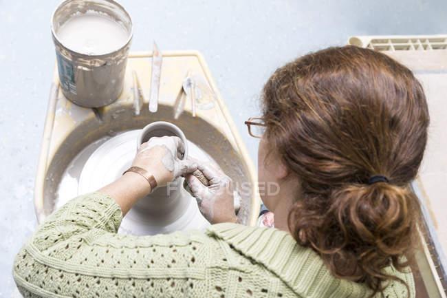 Woman working on potter wheel in studio — Stock Photo