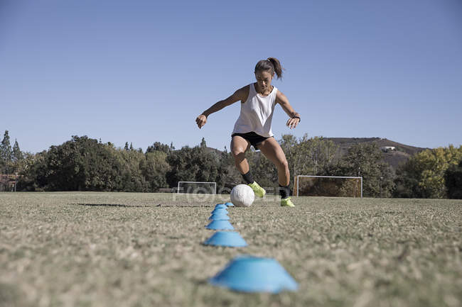 Young woman dribbling football on soccer pitch — Stock Photo