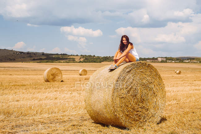 Woman sitting on top of hay bale — Stock Photo