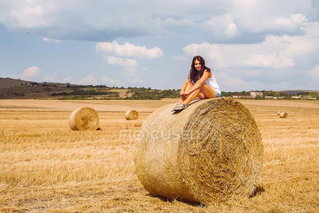 Mulher sentada em cima de fardos de feno — Fotografia de Stock