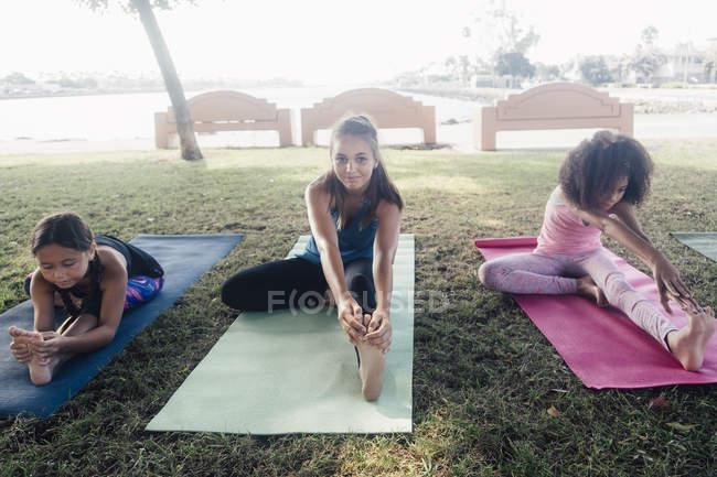 Три школьницы практикующие йогу позируют на школьной спортивной площадке — стоковое фото