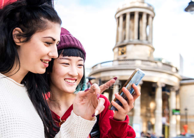 Two young stylish women looking at smartphone, London, UK — Stock Photo