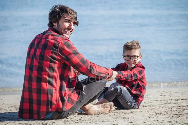 Padre e hijo sentados cara a cara en la playa - foto de stock