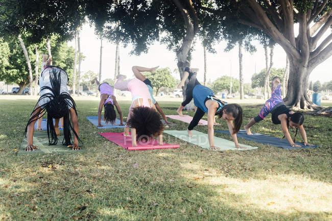 Школьницы практикуют йогу лицом вниз на школьном спортивном поле — стоковое фото