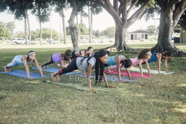 Школьницы практикующие йогу позируют на школьном спортивном поле — стоковое фото