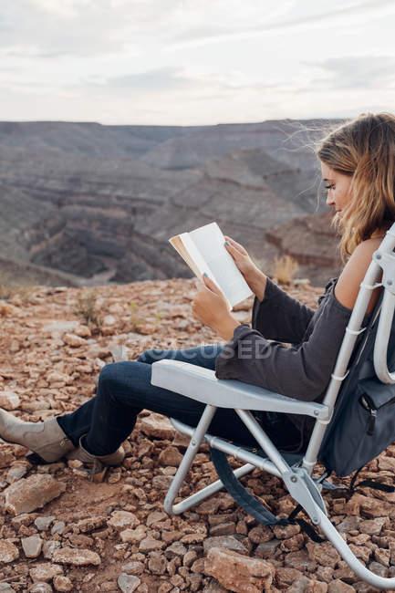 Jovem mulher sentada na cadeira de acampamento com livro, chapéu mexicano, Utah, EUA — Fotografia de Stock