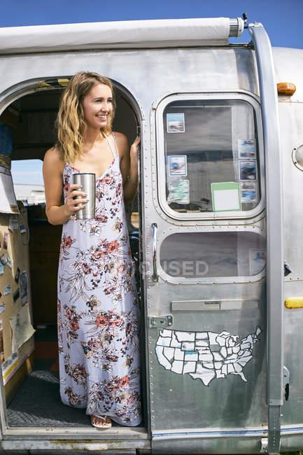 Junge Frau trägt Maxi-Kleid mit Blick vom Airstream Tür — Stockfoto