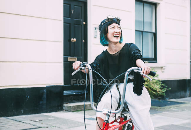 Young stylish woman cycling on retro bicycle — Stock Photo