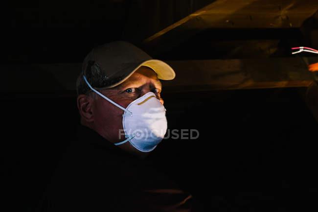 Man in dust mask looking sideways from dark loft — Stock Photo
