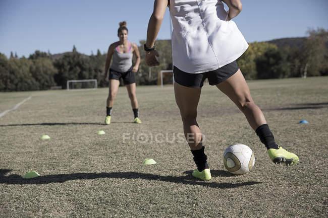 Junge Frauen am Fußballplatz, Fußball spielen — Stockfoto