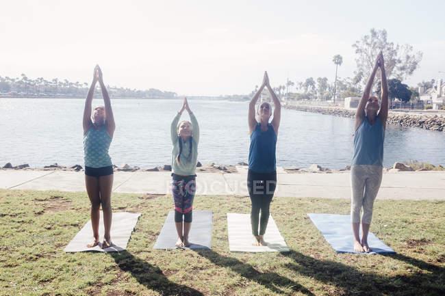 Школьницы, практикующие йогу в горной позе на школьной спортивной площадке — стоковое фото
