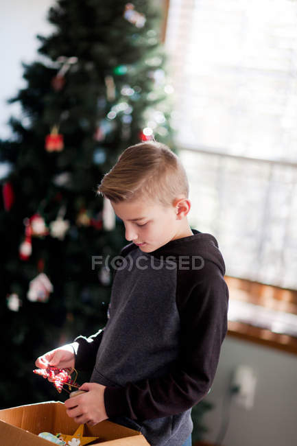 Boy holding decoration with Christmas tree at background — Stock Photo