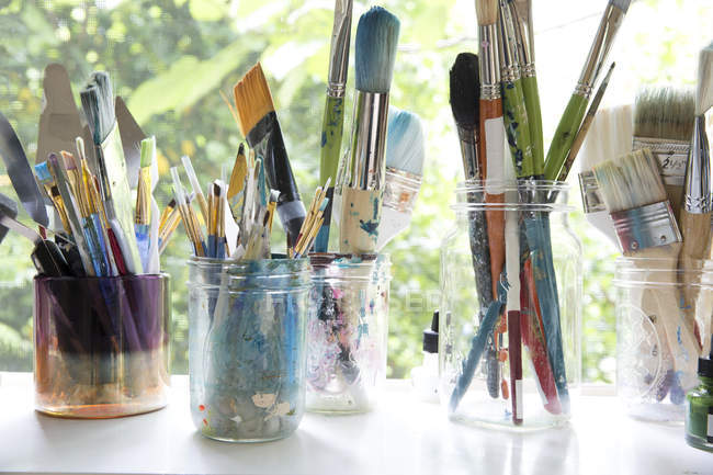 Row of jars with variety of artist paintbrushes on window sill  of artists studio — Stock Photo