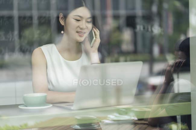 Femme d'affaires assise dans un café et utilisant un ordinateur portable, vue par la fenêtre — Photo de stock