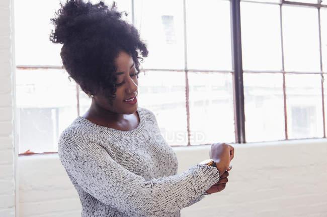 Женщина смотрит на часы в офисе — стоковое фото