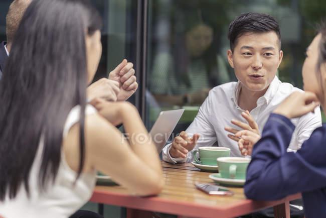 Quattro colleghi che parlano nel caffè all'aperto — Foto stock