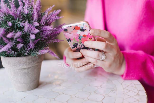 Jeune femme à l'aide de smartphone à table — Photo de stock