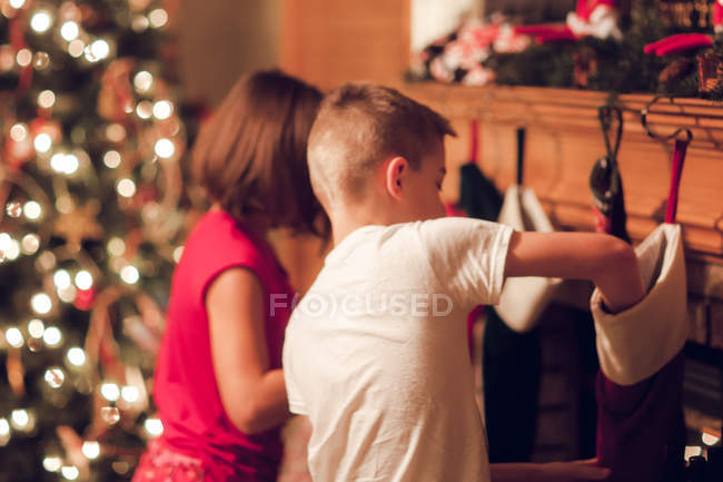 Brother and sister searching gifts in stockings on Christmas — Stock Photo