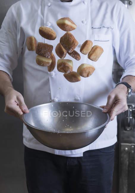 Recadrée vue du chef jetant des beignets et le sucre dans un bol — Photo de stock